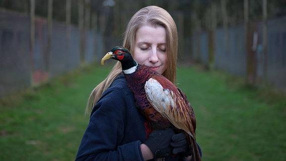 Blonde Frau hält Vogel auf dem Arm auf einem eingezäunten Feld.
