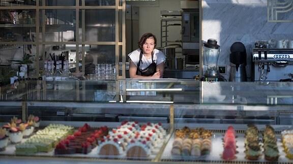 Frau lehnt an einer Durchreiche in einer Bäckerei. Im Vordergrund eine Auslage mit Kuchen.