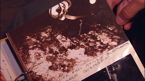 Hand an einem alten Bilderalbum