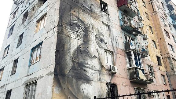 Graffiti einer Frau an einem Hochhaus.