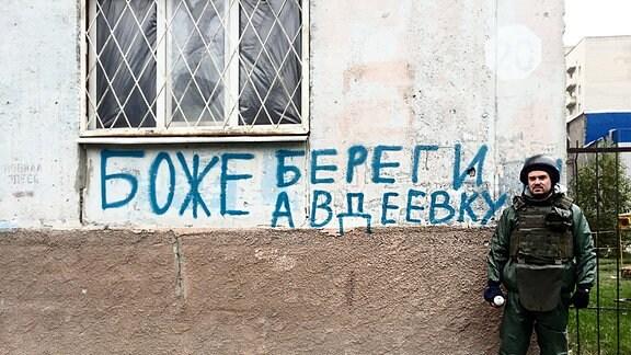 Russischer Text an einem Haus. Ein Armist steht daneben.