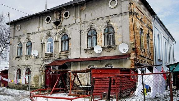 Eine alte, ehemalige Synagoge, an der außen Satelitenschüsseln angebracht sind und in der augenscheinlich Menschen leben