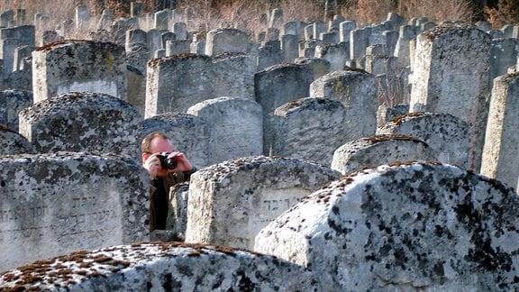 Ein Mann fotografiert zwischen jüdischen Grabsteinen