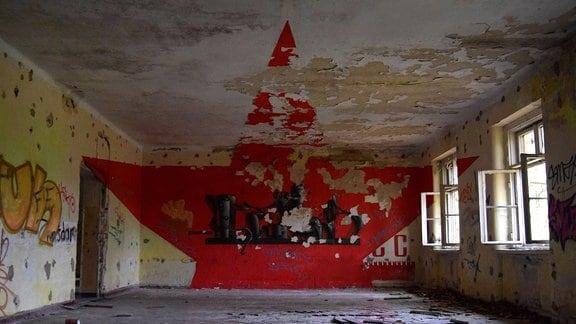 Bemalte Wand in einer verlassenen Kaserne. Die Farbe blättert ab.