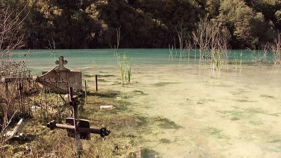 Grabkreuze ragen aus See