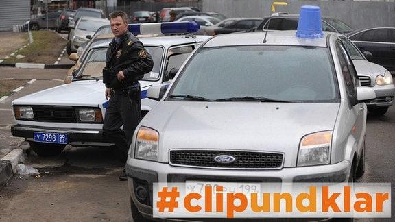 blauer Eimer auf einem Auto in Russland, daneben stehen ein Polizist und ein Polizeiwagen