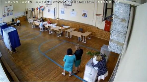 Frau steckt Wahlschein in Wahlurne