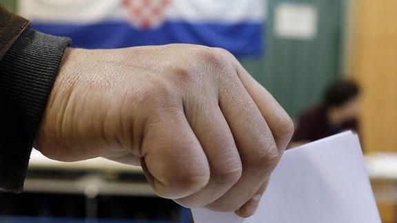 Eine Männerhand beim Einstecken eines Wahlzettels in eine Wahlurne. Him Hintergrund die Flagge Kroatiens.