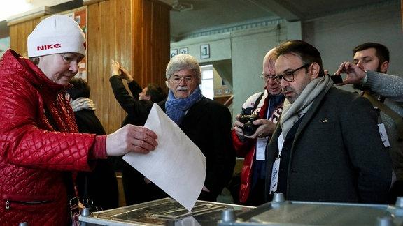 Wahlbeobachter schauen zu, wie eine Wählerin einen Stimmzettel in eine Wahlurne wirft.