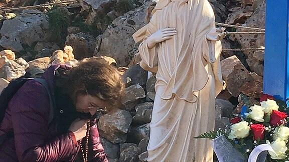 Eine Pilgerin legt eine Fürbitte vor die Marienstatue an einem der Erscheinungsorte. Es heißt, Gebete würden hier besonders erhört werden.