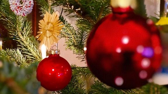 Weihnachtsbaum mit Kugeln und Strohsternen