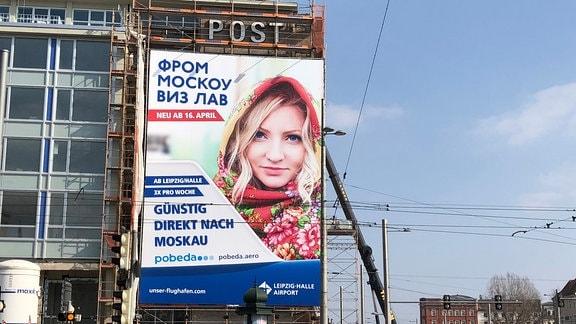 Pobeda-Werbeplakat am Leipziger Augustusplatz. Darauf steht in kyrillischer Umschrift From Moscou wiz law
