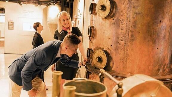 Blonde Frau und Mann im Anzug schauen in das Innere eines Brennkessels.