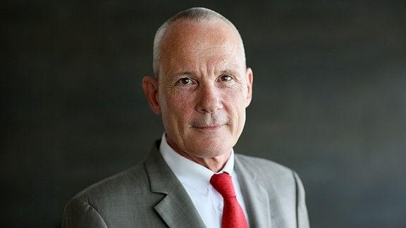 Portrait eines Mannes in grauem Anzug mit roter Krawatte.