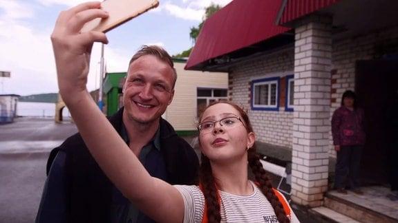 Ein Mädchen mit Brille macht ein Selfie von sich und einem Mann