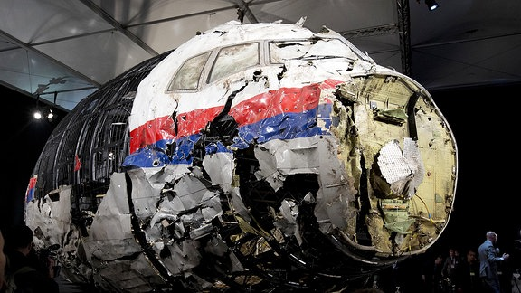 Die aus Trümmern wieder zusammen gesetzte Boeing 777, die als Flug MH17 über der Ukraine abgeschossen wurde, steht in einer Halle.