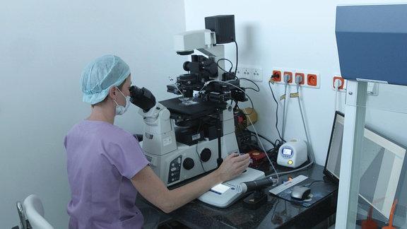 Eine Frau sieht durch ein Mikroskop