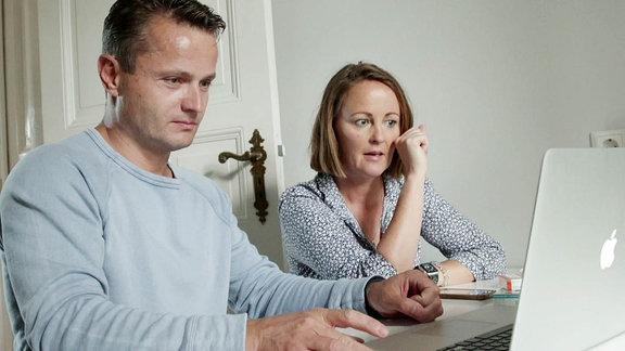 Ein Mann und eine Frau sitzen vor einem Laptop.