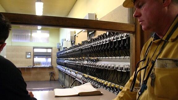 Arbeiter in gelbem Anzug an einer Ausgabe für Stirnlampen.