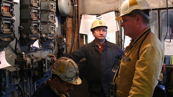 Drei Bergleute in einem Schaltraum.