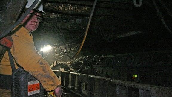 Bergbauarbeiter in einem dunklen Abbauschacht.