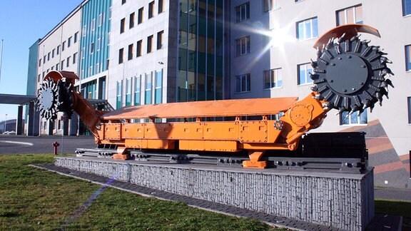 Orangenes Kohleabbaugerät mit zwei Abbaurädern vor einem hellen Bürogebäude.