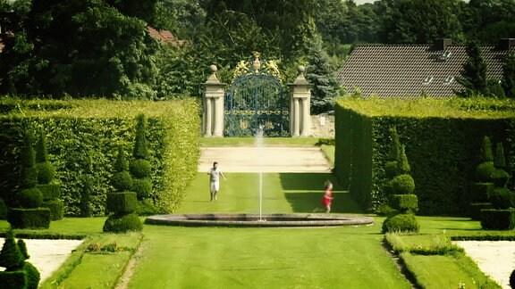 Ansicht eines Schlossparks mit Springbrunnen und saftig, grünen Hecken