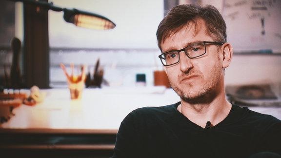 Ein junger Mann mit Brille sitzt vor seinem Schreibtisch