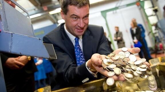Der Bayerische Staatsminister der Finanzen, Markus Söder (CSU), wühlt einer Kiste mit 2-Euromünzen