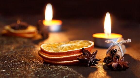 Zwei angezündete Teelichter, Zimtstangen, Anis und Orangenscheiben liegen auf einem dunklen Holz