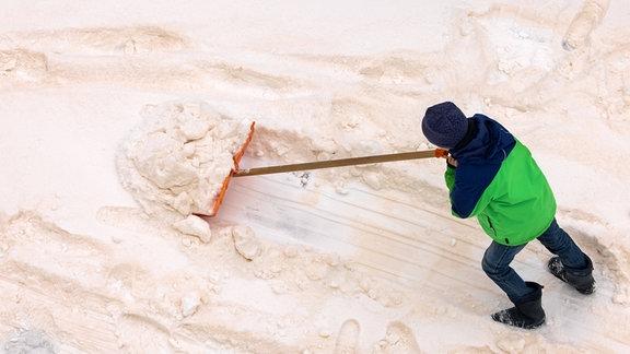 Ein Kind schiebt mit einem Schneeschieber eine Spur in den in Schichten gefärbten Schnee.