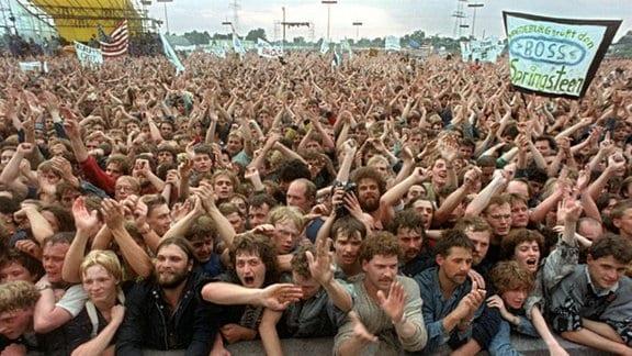 """Begeisterte Zuschauer bei einem Konzert des amerikanischen Rockmusiker Bruce Springsteen, auch """"The Boss"""" genannt, 1988 in Ostberlin."""
