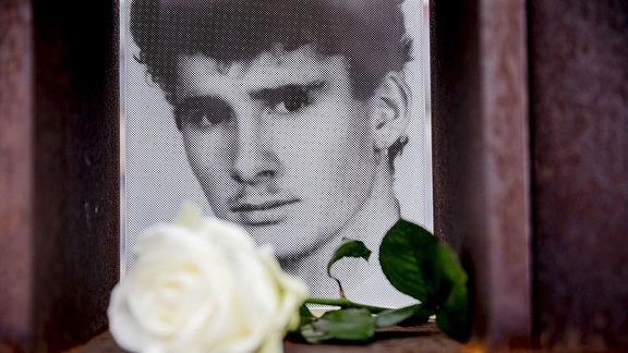 Das Bild von Chris Gueffroy mit einer weißen Rose ist am Fenster des Gedenkens für die Todesopfer der Berliner Mauer auf dem früheren Todesstreifen an der Bernauer Straße zu sehen.
