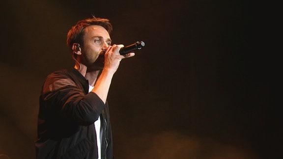 Clueso steht auf einer Bühne uns singt in sein Mikrofon