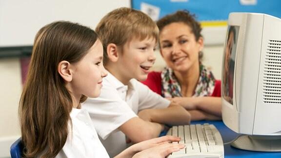 Zwei Kinder sitzen mit ihrer Mutter vor dem Computer.