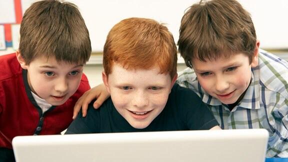 Drei Jungs starren gespannt auf einen Monitor.