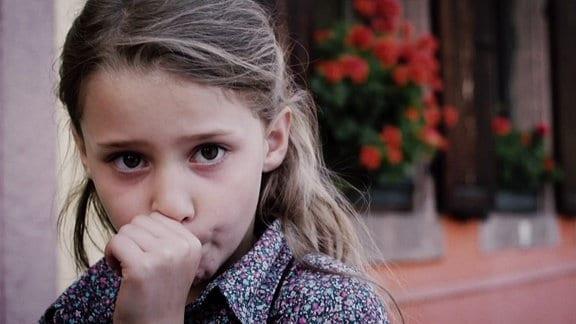 Ein kleines Mädchen hat ihren Daumen im Mund