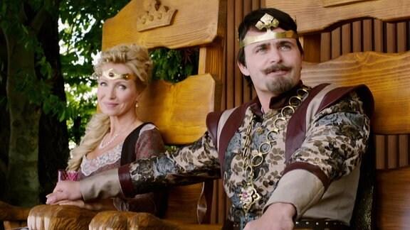 Eine Königin und ein König sitzen im Freien auf ihren Trohn