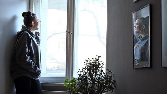 Eine junge Frau steht allein am Fenster und schaut hinaus.