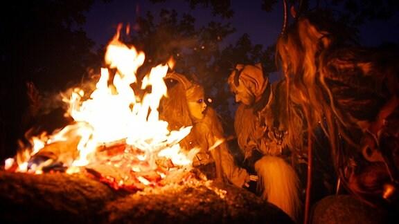 Zwei maskierte Personen tanzen um ein Feuer in der Nacht