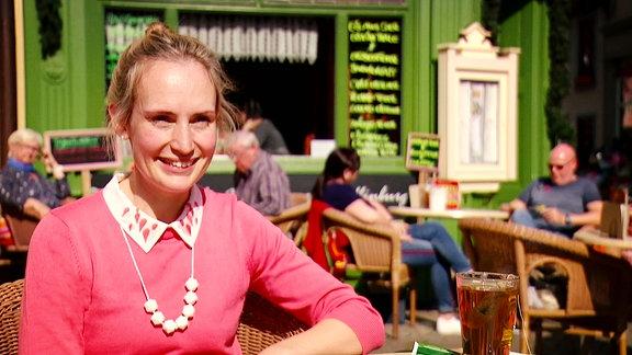 Eine junge Frau sitzt in einem Cafe und erzählt