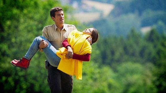 Ein Junger Mann (der Ranger) trägt ein bewusstloses Mädchen
