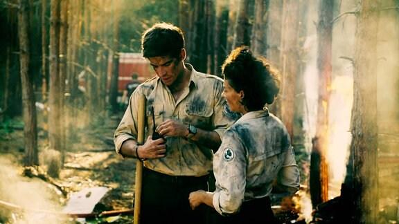 Der Ranger und seine Kollegin stehen erschöpft in einem verbrannten Wald
