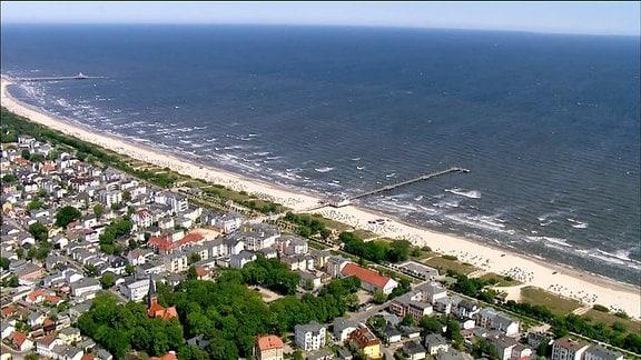 Luftbild eines Ostseestrandes und der angrenzenden Ortschaft.