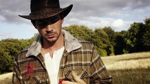Ein Mann mit Cowboyhut hat eine Schussverletzung auf seiner Brust. Mit seiner Hand hat er die Wunde abgetastet und bemerkt, dass er blutet.