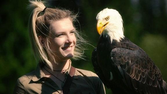 Eine Falknerin trägt einen Seeadler auf dem Arm und lächelt