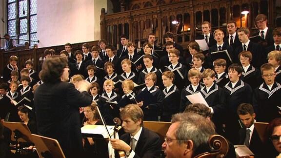Der Thomanerchor singt in einer großen Aula