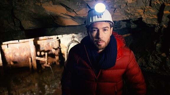 Der Moderator, ein junger Mann steht mit Helm in einem Bergwerksschacht