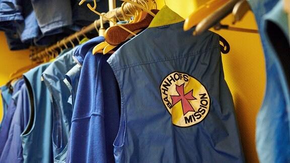 Arbeitskleidung für ehrenamtliche Helfer der Berliner Bahnhofsmission am Zoologischen Garten Berlin hängen an einer Garderobe.
