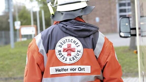 Ehrenamtlicher DRK-Mitarbeiter mit der Rückaufschrift Helfer vor Ort.
